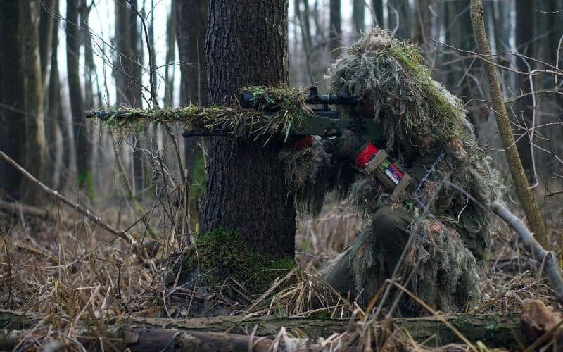 airsoft sniper aiming in a gillie suit