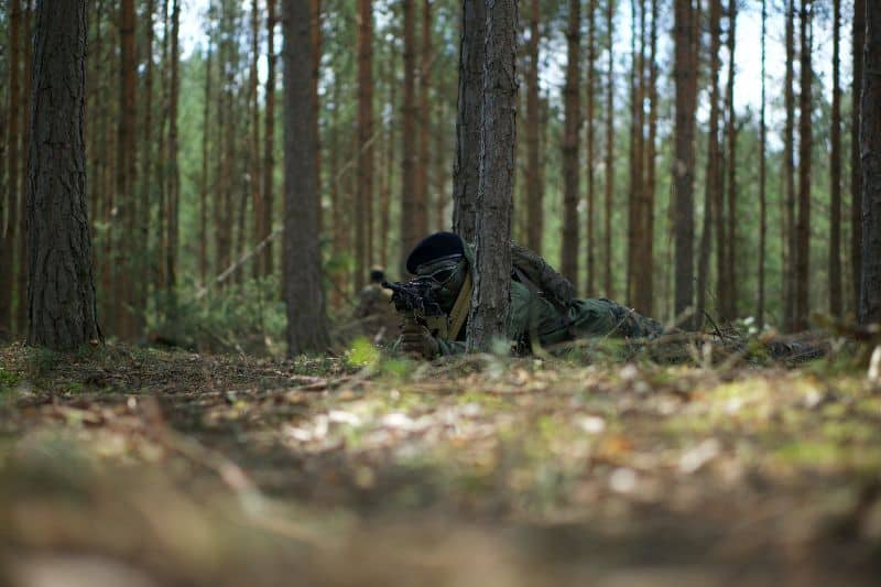 sniper laying down aiming in the woods